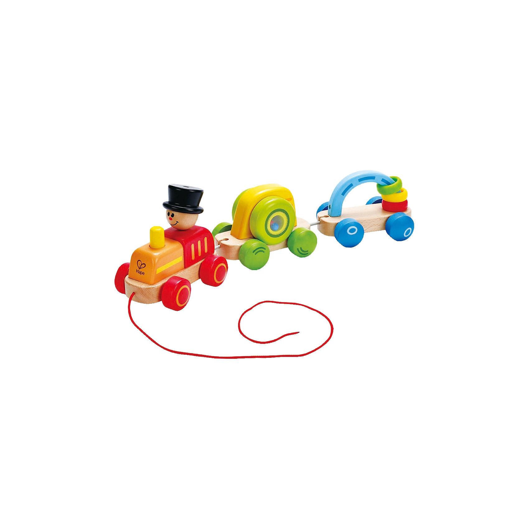 Каталка Паровозик, HapeИгрушки для малышей<br>Каталка Паровозик, Hape (Хейп).<br><br>Характеристики:<br><br>- Материал: древесина, краска на водной основе, PC, PE<br>- Размер: 8,8х8,8х16 см.<br><br>Игровой набор состоит из паровозика и 2-х вагонов, которые можно отсоединять друг от друга и играть отдельно. У паровозика длинная веревка, с помощью которой малышу удобно катать игрушку. Внутри первого вагона находятся разноцветные шарики, они весело гремят при движении. У второго вагона есть арка, на которую нанизаны разноцветные колечки, их можно перекидывать с одной стороны арки на другую. Яркие цвета и подвижные элементы привлекают внимание малыша, побуждают к изучению и движению, также игрушка способствует развитию моторики, координации.<br><br>Каталку Паровозик, Hape (Хейп) можно купить в нашем интернет-магазине.<br><br>Ширина мм: 421<br>Глубина мм: 187<br>Высота мм: 96<br>Вес г: 858<br>Возраст от месяцев: 12<br>Возраст до месяцев: 24<br>Пол: Унисекс<br>Возраст: Детский<br>SKU: 4141516