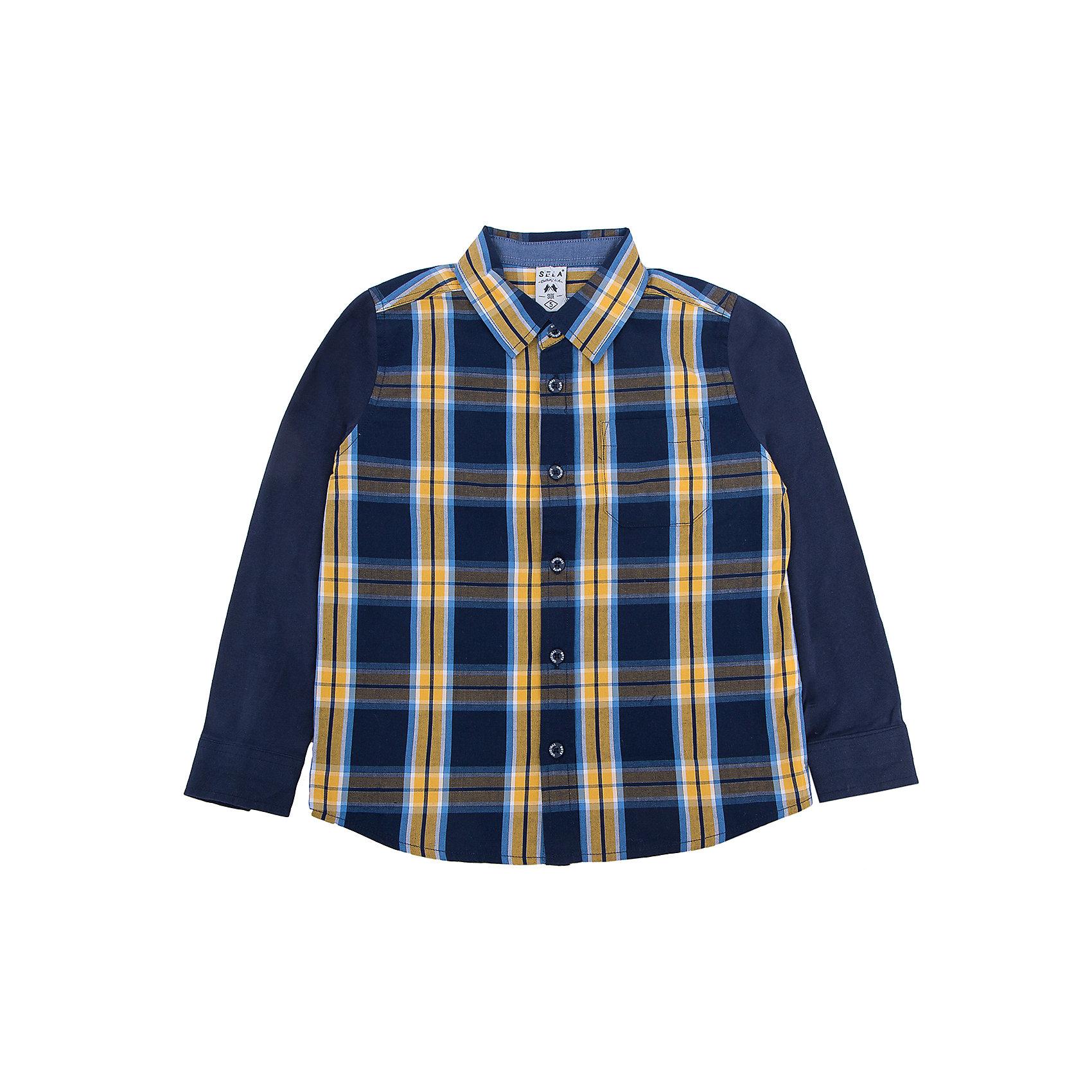 Рубашка для мальчика SELAБлузки и рубашки<br>Удобная рубашка - незаменимая вещь в гардеробе школьников. Эта модель отлично сидит на ребенке, она сделана из приятного на ощупь материала, мягкая и дышащая. Натуральный хлопок в составе ткани не вызывает аллергии и обеспечивает ребенку комфорт. Модель станет отличной базовой вещью, которая будет уместна в различных сочетаниях.<br>Одежда от бренда Sela (Села) - это качество по приемлемым ценам. Многие российские родители уже оценили преимущества продукции этой компании и всё чаще приобретают одежду и аксессуары Sela.<br><br>Дополнительная информация:<br><br>цвет: разноцветный;<br>материал: 100 % хлопок;<br>рукава длинные;<br>застежки - пуговицы.<br><br>Рубашку для мальчика от бренда Sela можно купить в нашем интернет-магазине.<br><br>Ширина мм: 174<br>Глубина мм: 10<br>Высота мм: 169<br>Вес г: 157<br>Цвет: синий<br>Возраст от месяцев: 48<br>Возраст до месяцев: 60<br>Пол: Мужской<br>Возраст: Детский<br>Размер: 110,92,98,116,104<br>SKU: 4913040