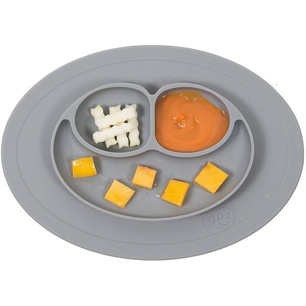 Тарелка малая с подставкой Mini Mat, 240 мл., ezpz, серыйДетская посуда<br>Тарелка с подставкой Mini Mat, ezpz, серый.<br><br>Характеристики:<br>• изготовлена из качественного пищевого силикона<br>• надежно крепится к столу<br>• 3 отсека для еды<br>• удобно брать с собой<br>• подходит для посудомоечной машины и микроволновой печи<br>• не содержит бисфенол, свинец, фталаты, поливинилхлорид<br>• приятный дизайн<br>• состав: 100% силикон<br>• размер: 21,5х19,5х2,5 см<br>• объем: 240 мл<br>• цвет: серый<br><br>Тарелка с подставкой Mini Mat, ezpz пригодится, если в доме живут маленькие непоседы. Тарелка имеет 3 глубоких отсека, что позволяет подавать еду раздельно. Вы сможете одновременно подать к столу мясо, гарнир и фрукты, не пачкая лишнюю посуду. Дно тарелки надежно крепится к плоской поверхности - вы можете не переживать, что малыш опрокинет еду и обожжется. Небольшой размер позволит брать тарелку с собой в дорогу. Приятный дизайн тарелки понравится ребенку, и он обязательно будет есть с аппетитом!<br><br><br>Вы можете купить тарелку с подставкой Mini Mat, ezpz, серый в нашем интернет-магазине.<br>Ширина мм: 210; Глубина мм: 25; Высота мм: 195; Вес г: 323; Возраст от месяцев: 0; Возраст до месяцев: 36; Пол: Унисекс; Возраст: Детский; SKU: 5068714;