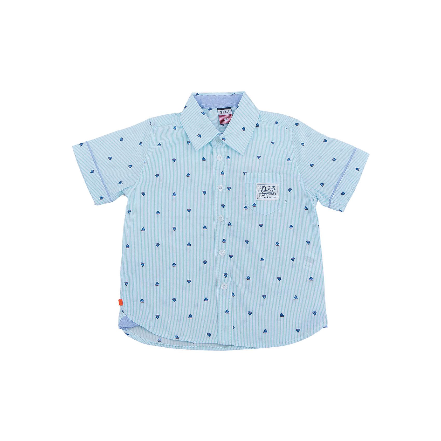 Рубашка для мальчика SELAБлузки и рубашки<br>Характеристики товара:<br><br>• цвет: голубой<br>• сезон: лето<br>• состав: 100% хлопок<br>• пуговицы<br>• короткие рукава<br>• отложной воротник<br>• принт<br>• страна бренда: Россия<br><br>Модная рубашка для мальчика разнообразит гардероб ребенка. Она отлично сочетается с джинсами, брюками или шортами. Очень стильно смотрится!<br><br>Одежда, обувь и аксессуары от российского бренда SELA не зря пользуются большой популярностью у детей и взрослых! Модели этой марки - стильные и удобные, цена при этом неизменно остается доступной. <br><br>Рубашку для мальчика от популярного бренда SELA (СЕЛА) можно купить в нашем интернет-магазине.<br><br>Ширина мм: 174<br>Глубина мм: 10<br>Высота мм: 169<br>Вес г: 157<br>Цвет: голубой<br>Возраст от месяцев: 60<br>Возраст до месяцев: 72<br>Пол: Мужской<br>Возраст: Детский<br>Размер: 116,92,98,104,110<br>SKU: 5305538